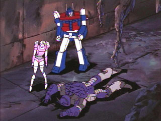 Arcee and Magnus standing next to a face-planted Galvatron